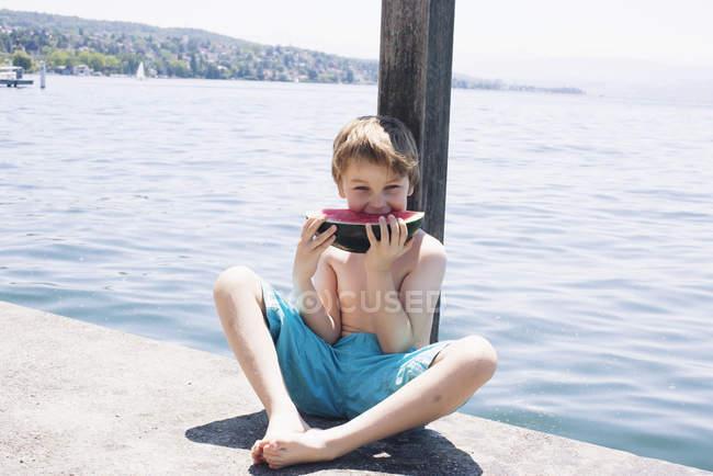 Rapaz comendo melancia na doca — Fotografia de Stock