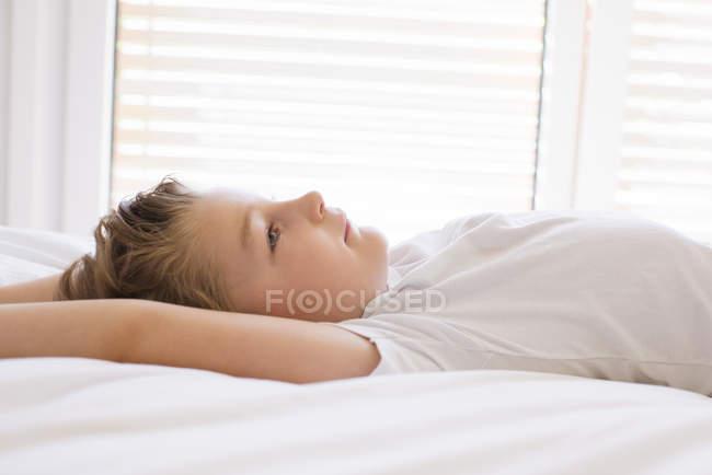 Vista lateral do garoto relaxante na cama — Fotografia de Stock