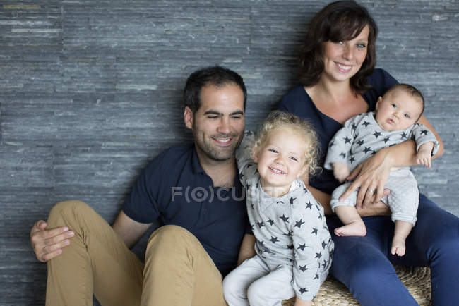 Retrato de familia con dos niños pequeños sentados en la cama en casa - foto de stock