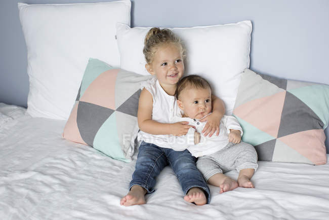 Little girl with baby brother sitting on the bed — Stock Photo