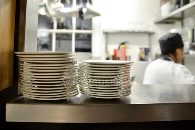 Montón de placas en estante en la cocina comercial - foto de stock