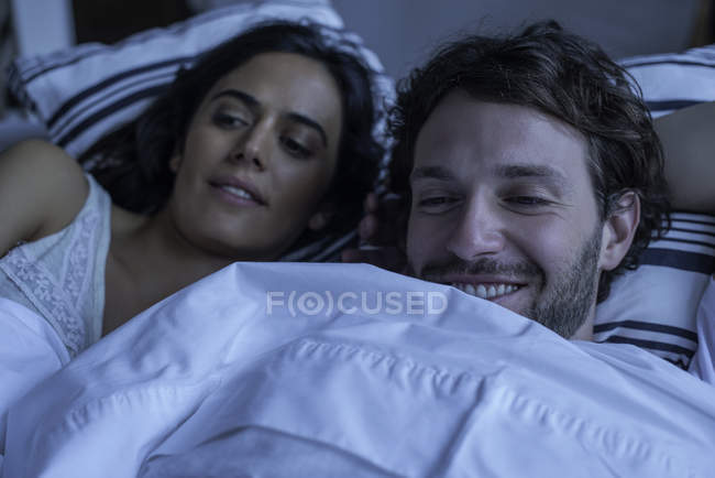 Couple watching tv together in bed — Stock Photo