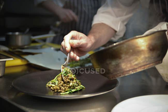 Prato de lentilha namorando chef no prato de servir — Fotografia de Stock