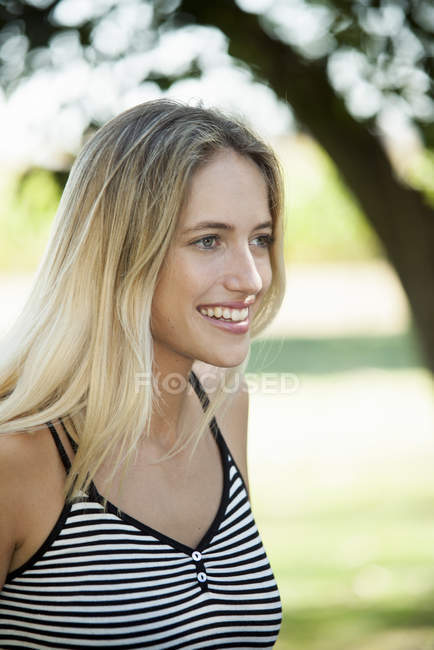 Portrait of smiling blonde woman looking away outdoors — Stock Photo