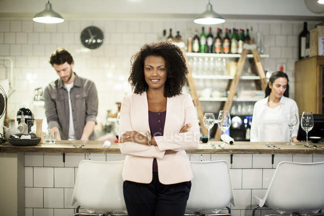 Portrait of cafe owner with coworkers on the background — Stock Photo