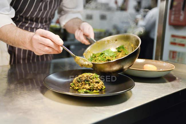 Шеф-повар ресторана размещение приготовленной чечевицы блюдо на плите — стоковое фото
