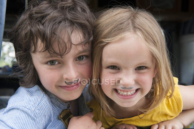 Portrait of young siblings with drawing fake mustaches — Stock Photo