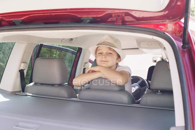 Garçon à la recherche sur la banquette arrière de voiture — Photo de stock