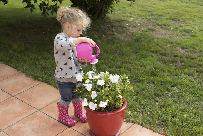 Little girl watering potted plants — Stock Photo