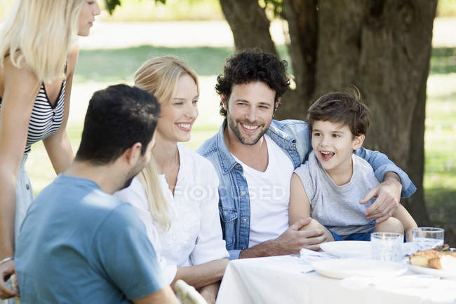 Friends enjoying meal and talking outdoors — Stock Photo