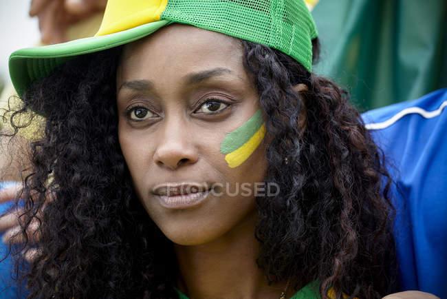 Brazilian football fan wearing hat and face paint — Stock Photo