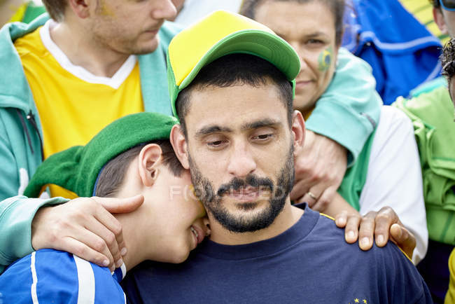 Brazilian football fans consoling each other at match — Stock Photo