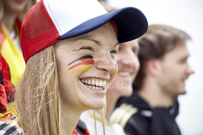 German football fan smiling at match — Stock Photo