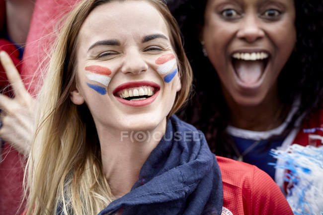 French football fans smiling and cheering at match — Stock Photo