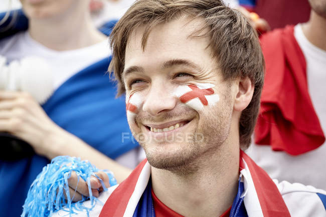 British football fan smiling cheerfully at match — Stock Photo
