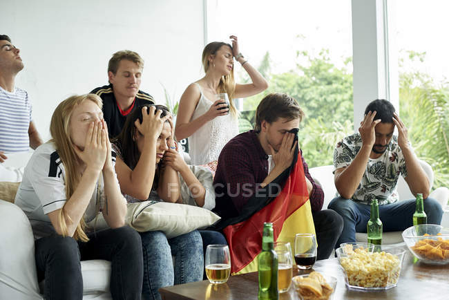 German football fans watching football match at home — Stock Photo