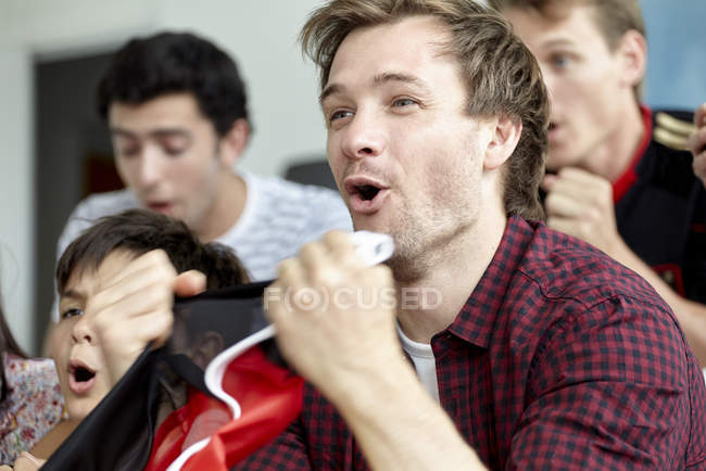 Football enthusiasts cheering while watching match at home — Stock Photo
