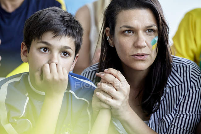 Mother and son watching football match at home — Stock Photo