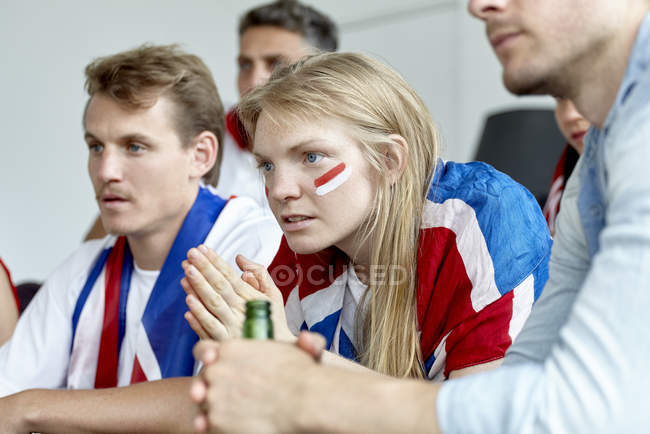 British football fans watching match together at home — Stock Photo