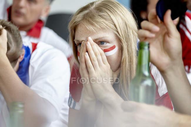 Mulher segurando as mãos sobre o rosto em decepção ao assistir esportes jogo em casa — Fotografia de Stock