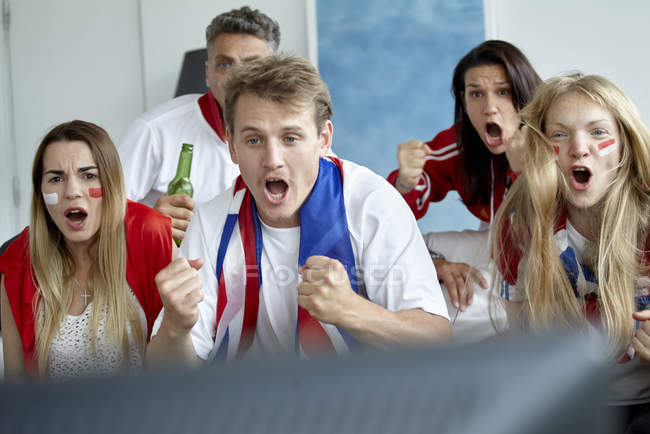 British football fans cheering while watching match on TV — Stock Photo