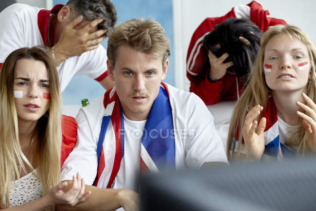 British football supporters looking upset while watching match on TV — Stock Photo