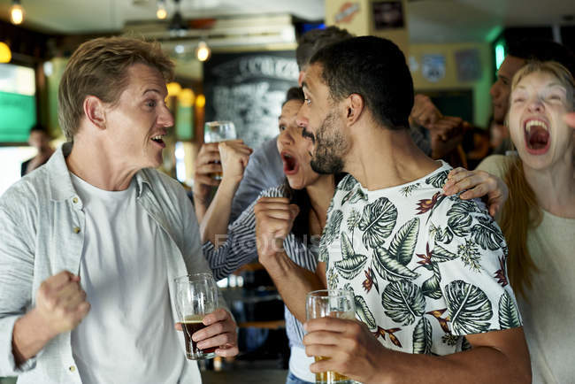 Fãs de futebol comemorando juntos no pub — Fotografia de Stock