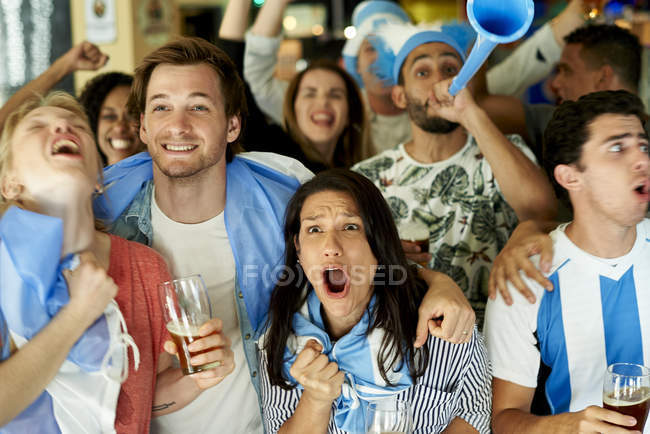 Argentinian soccer fans watching match together at pub — Stock Photo