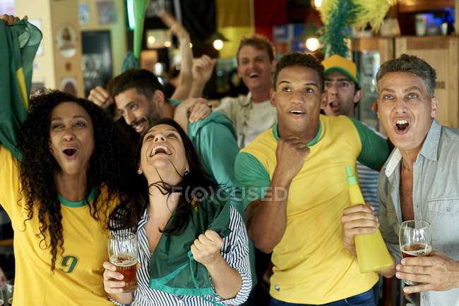 Happy Brazilian soccer fans watching match together at pub — Stock Photo
