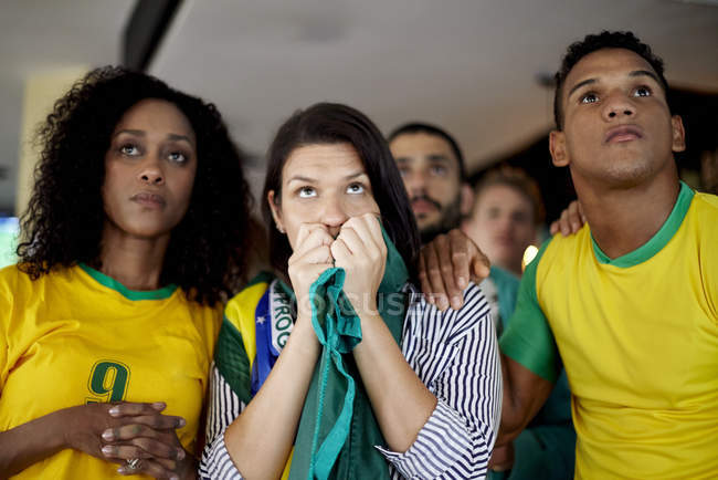 Brazilian football supporters anxiously watching match in bar — Stock Photo