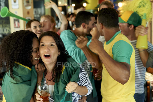 Brazilian soccer fans watching match together at pub — Stock Photo