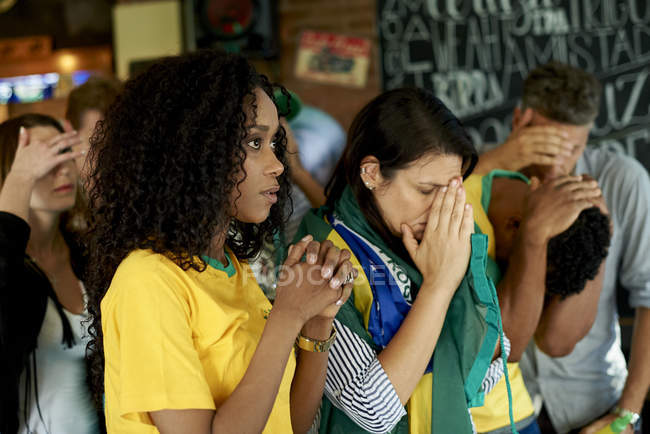 Sad Brazilian soccer fans watching match together at pub — Stock Photo