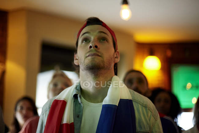 French football fan watching match in bar — Stock Photo