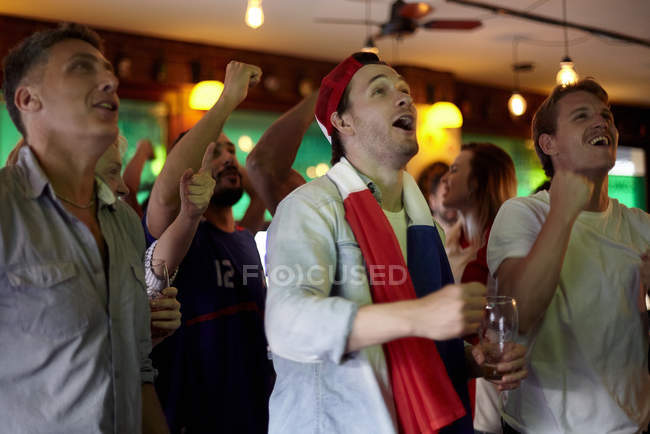 French football fans watching match in bar — Stock Photo