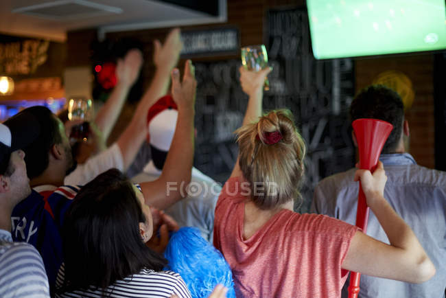 French football fans watching soccer match on television at pub — Stock Photo