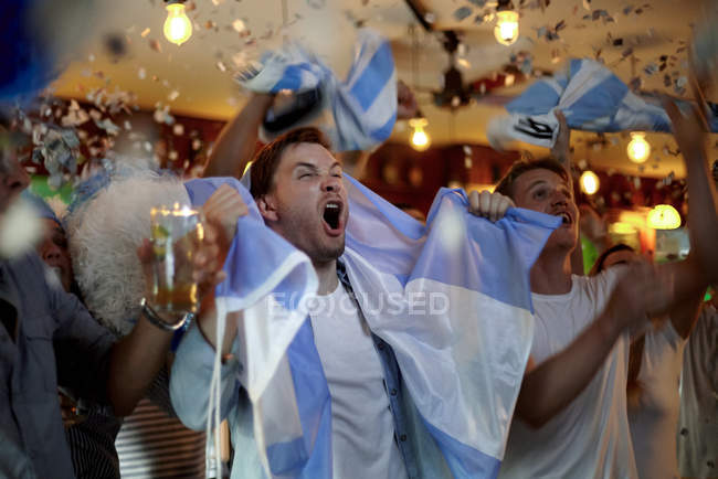 Argentinian football fans celebrating victory in bar — Stock Photo