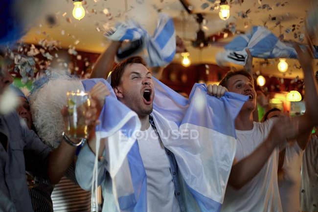 Os fãs de futebol argentino comemorando a vitória em bar — Fotografia de Stock
