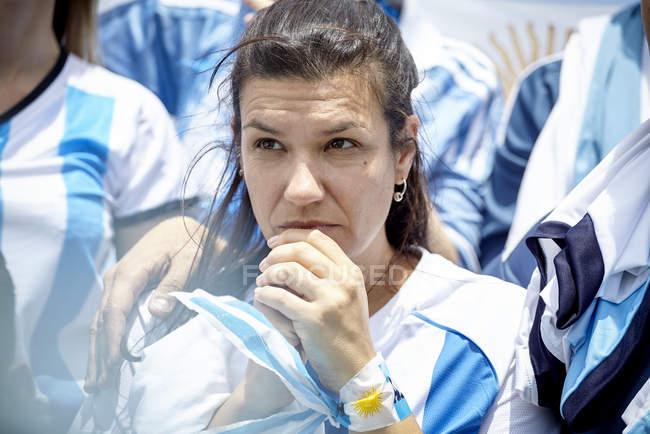 Аргентинский футбольный фанат смотрит матч с тревожным выражением лица — стоковое фото
