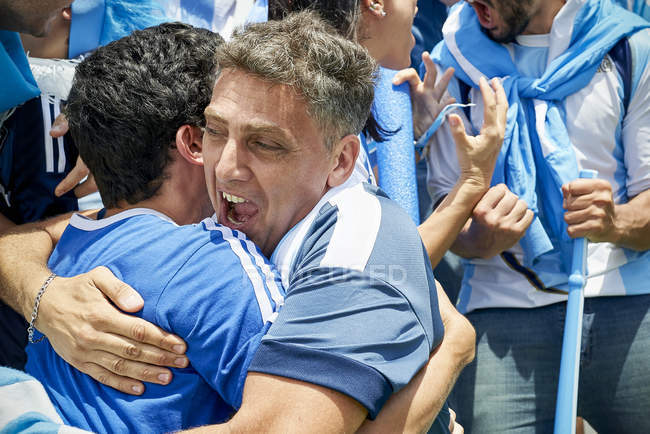 Argentinian football fans embracing at football match — Stock Photo