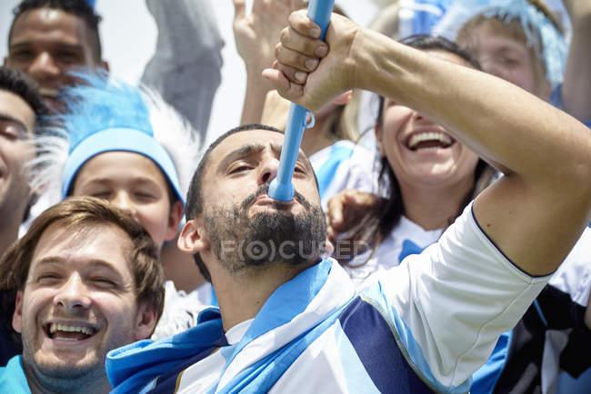 Argentinian football fan playing vuvuzela at match — Stock Photo
