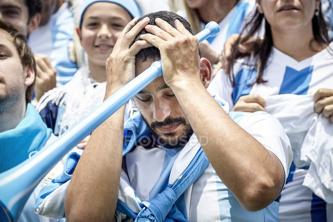 Argentinian football fan holding head in disappointment at match — Stock Photo