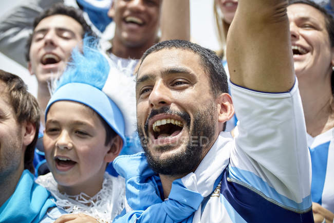 Football fans in colorful clothing cheering at match — Stock Photo