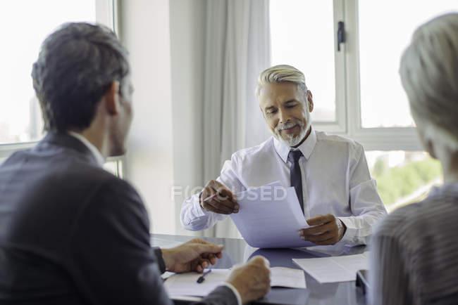 Mature homme d'affaires réunion avec couple dans le bureau — Photo de stock