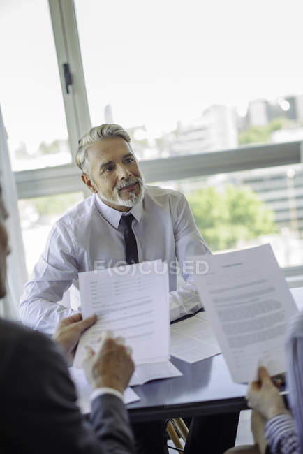 Mature businessman meeting with couple in the office — Stock Photo