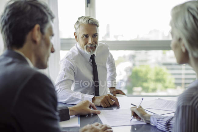 Woman signing document in meeting with business professionals — Stock Photo