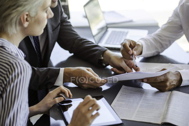 Mature businessman explaining document to colleagues in the office — Stock Photo