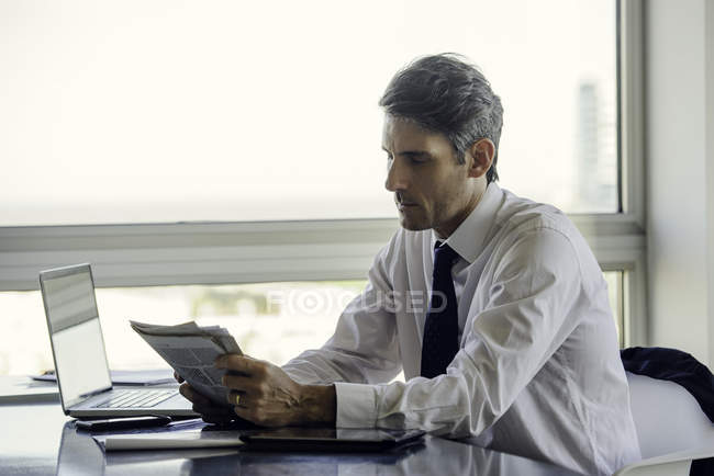 Man reading newspaper in office — Stock Photo