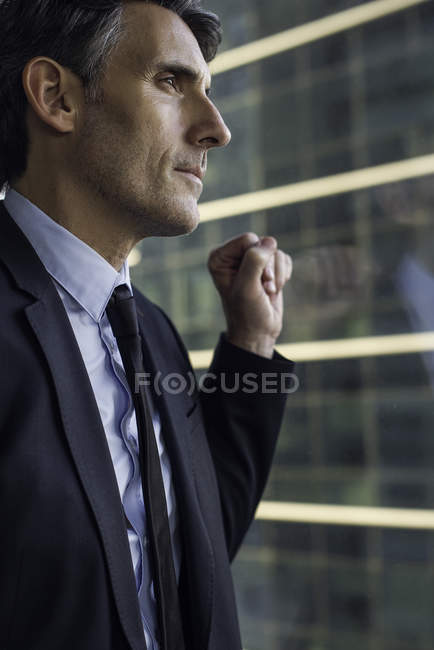 Man looking through window in high rise building — Stock Photo