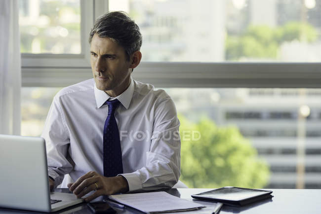 Man using laptop computer in office — Stock Photo