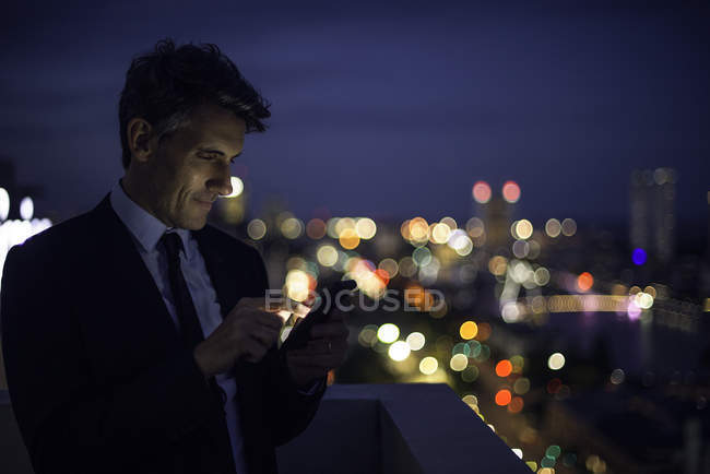 Businessman on high rise rooftop using mobile phone — Stock Photo